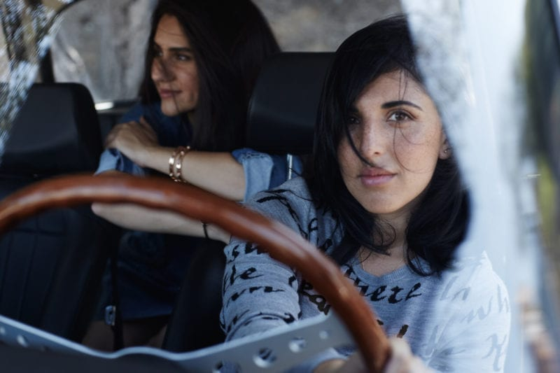 Two women in a car, one in the driver's seat