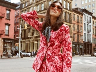 A woman in a pink, velour outfit standing in front of a building in downtown L.A.