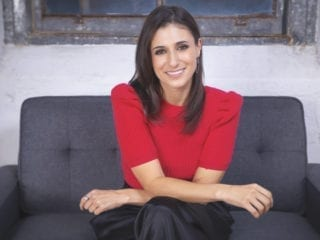 A smiling woman wearing read and seated on a couch
